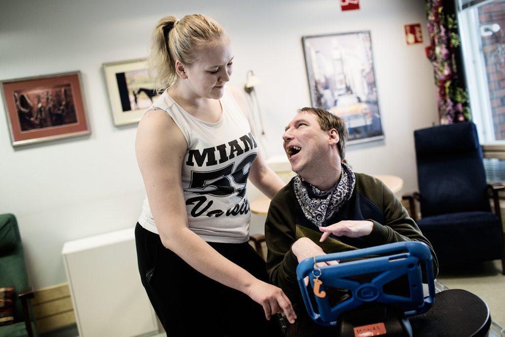 Joonas Rajamäki juttelee hoitajan kanssa Åvikin palvelukeskuksessa.